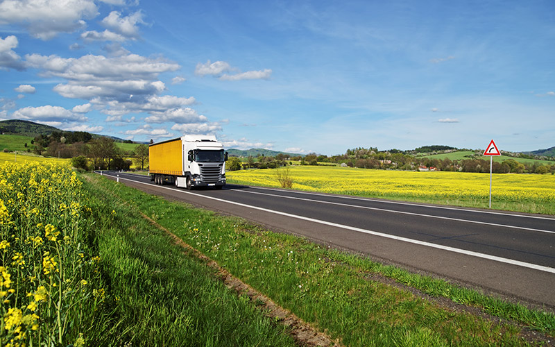 Truck driving on road with yellow fields on either side