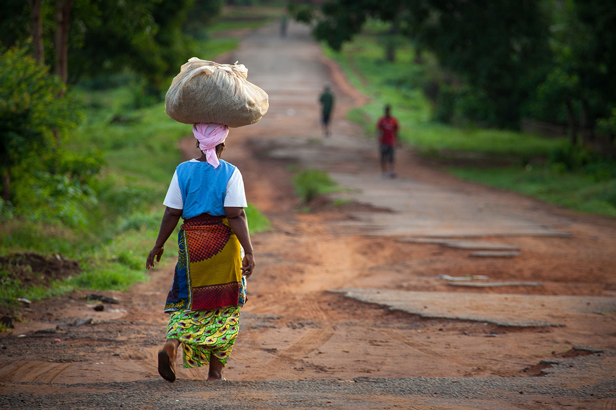 Woman in Africa carrying laundry on her head