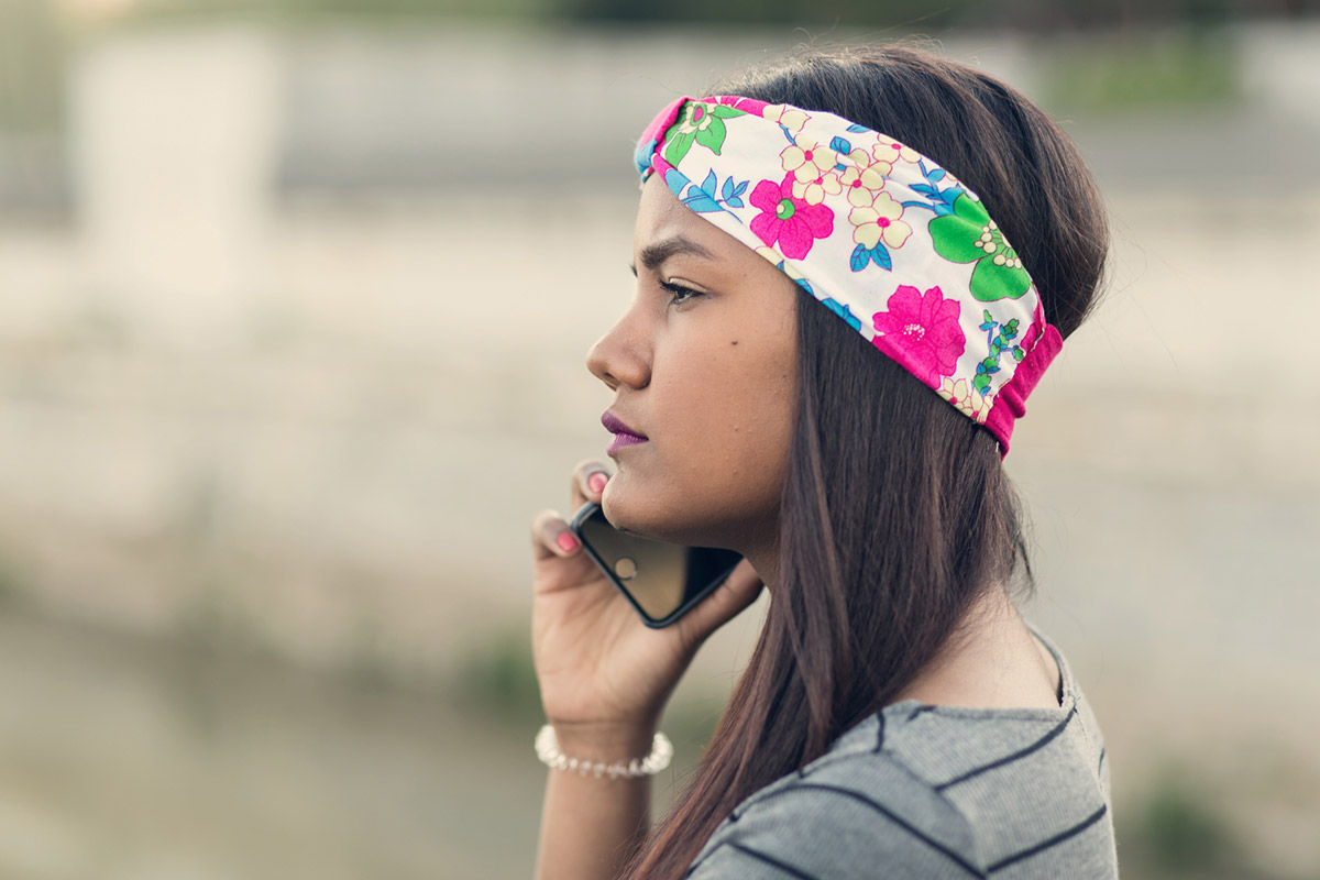 Young girl with headband talking on mobile phone