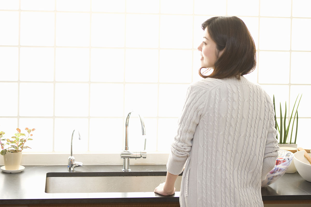 Woman standing by kitchen sink