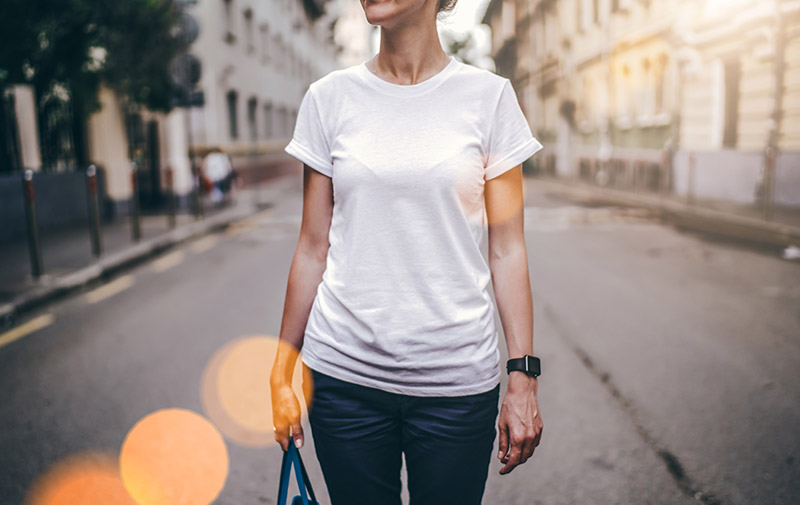 Woman standing in a city street in jeans and white t-shirt
