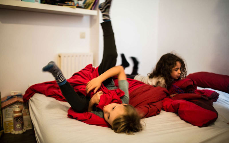 Two kids playing on a bed with red sheets