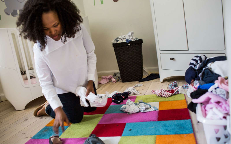 Woman on the floor of child's room sorting laundry