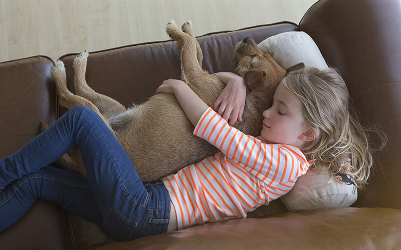 Girl lying on a brown leather couch while hugging a dog