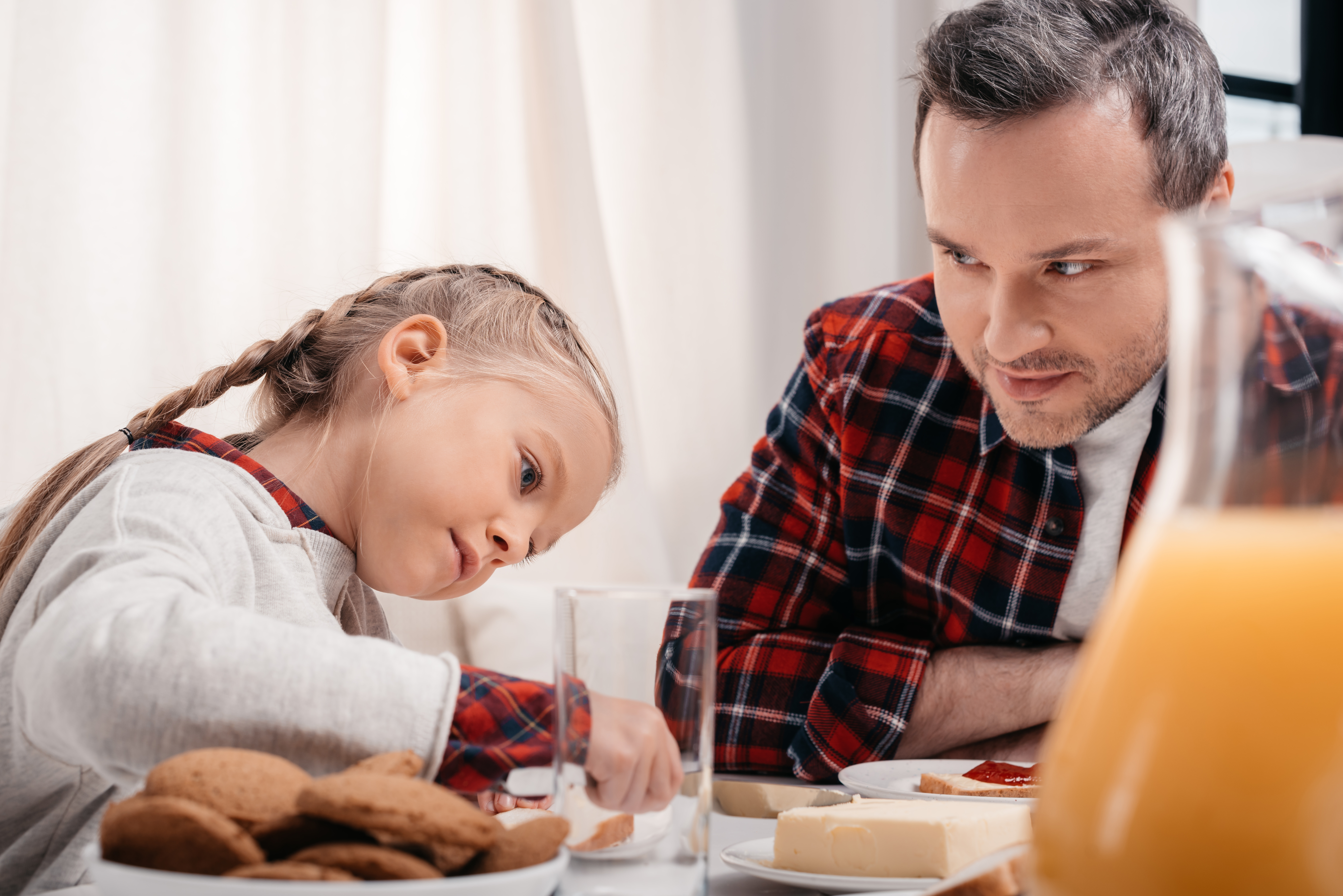 Father and daughter sitting at table with juice and cookies