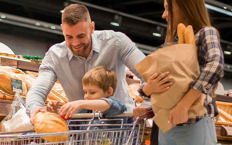 Man and woman and small boy in a supermarket picking bread off the shelves