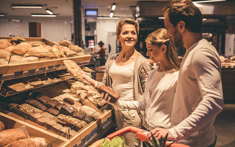 Two women and a man standing in a supermarket looking at shelves of freshly baked bread