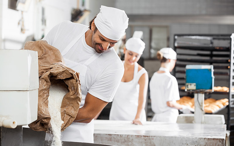 An industrial bakery with a man in the foreground pouring flour out of a bag