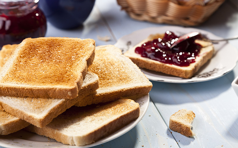 A plate with a pile of toast and a plate with one piece of toast with jam