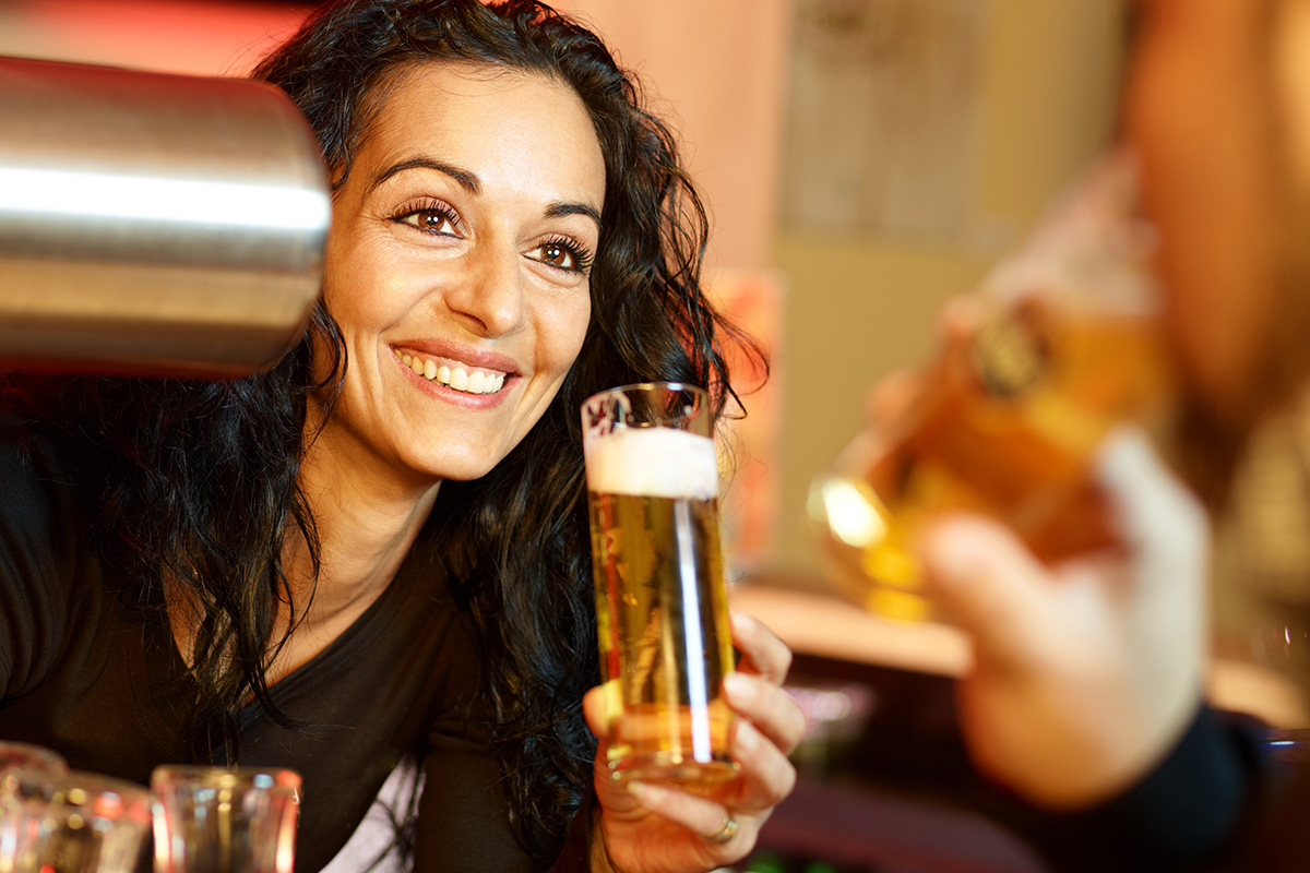 Dark haired woman smiling with a beer in her hand