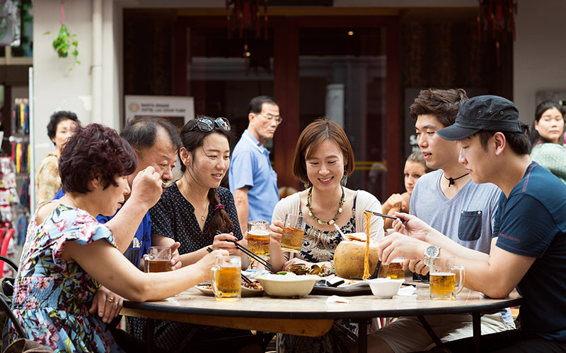 A group of Chinese people having dinner and beer outside at a round table