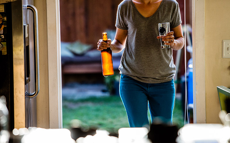 Woman in grey shirt walking with a bottle of beer and an empty glass in her hands