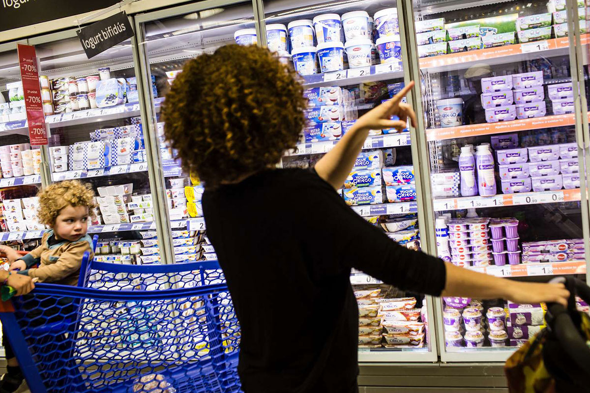 Woman pointing at the dairy cabinet in a supermarket