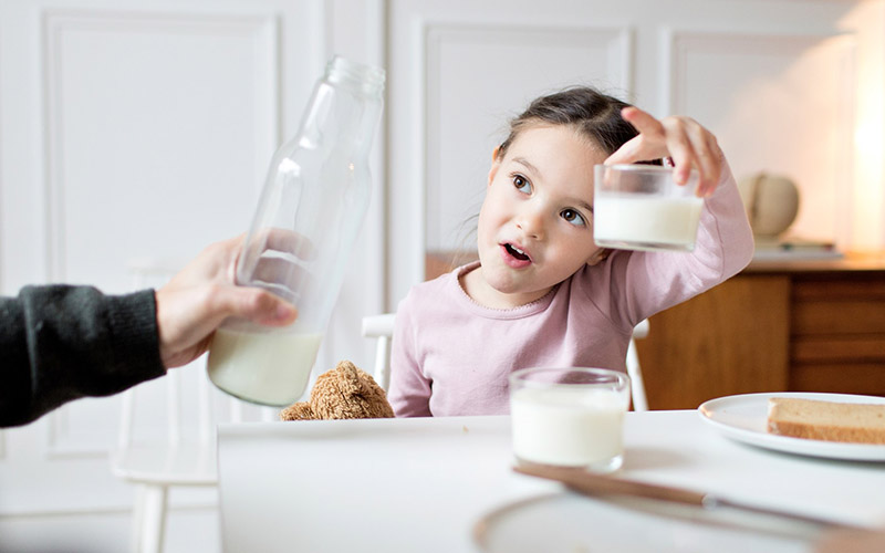 Little girl holding up her glass of milk