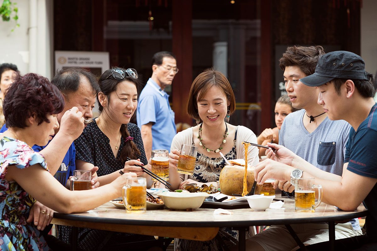 Chinese family having dinner outside and drinking beers at a round table