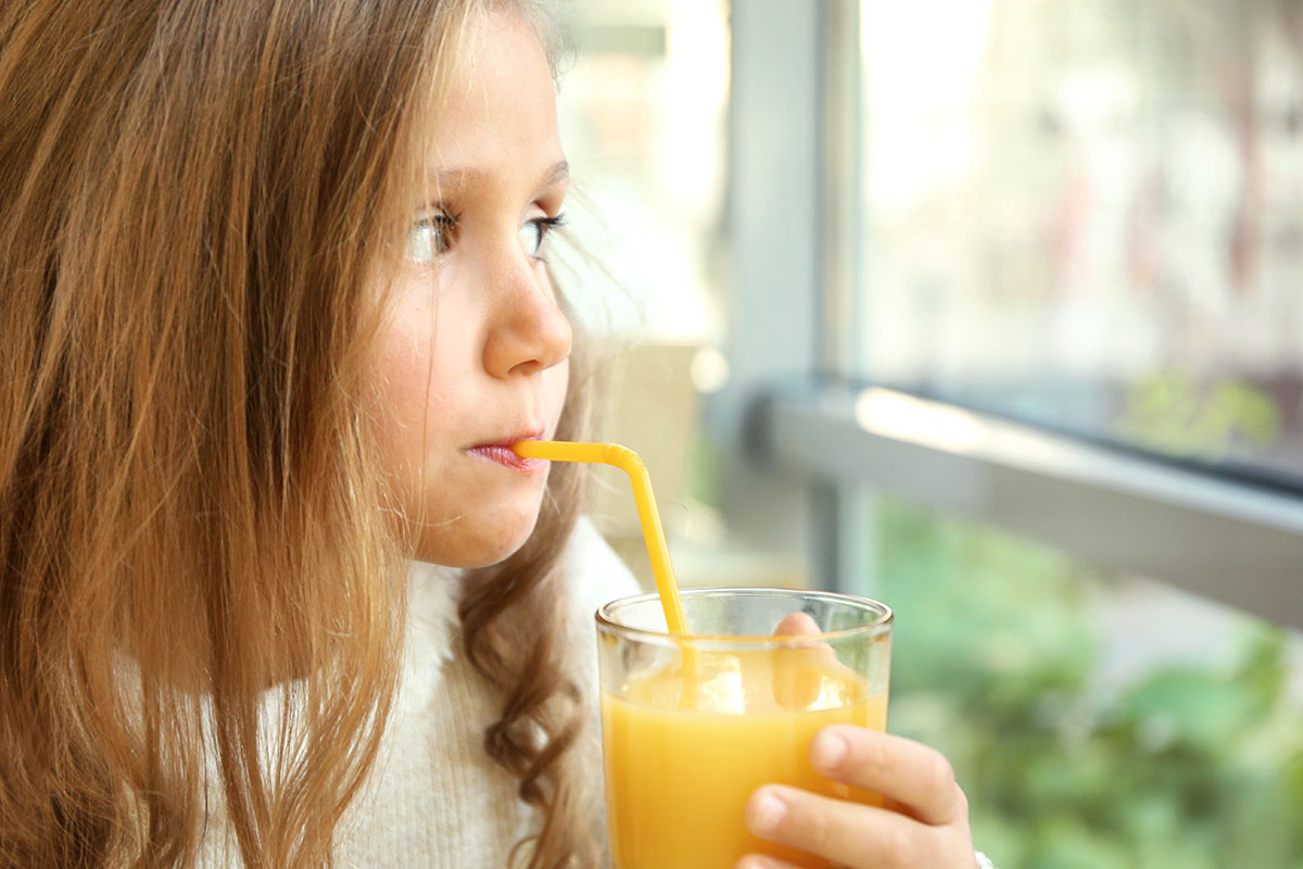 Little girl drinking orange juice with a straw