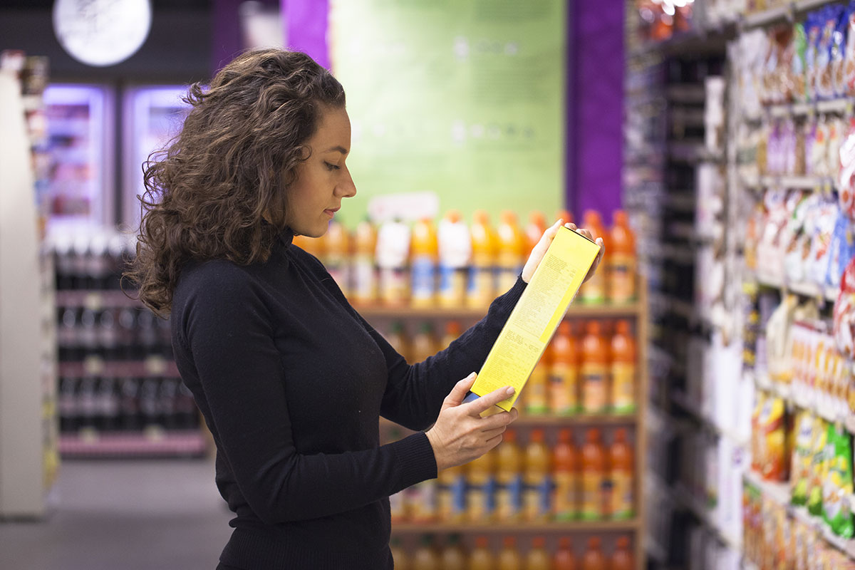 Woman reading the back of a cereal box at a supermarket
