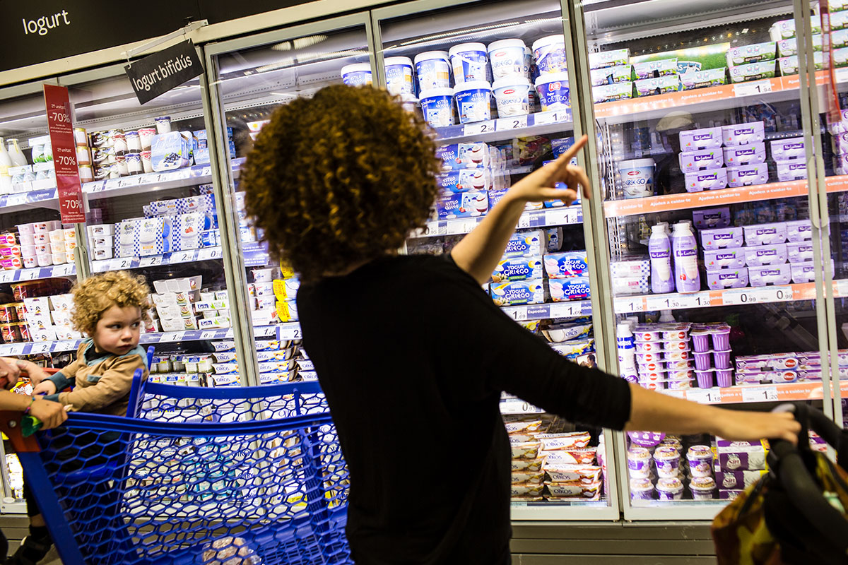 Woman pointing at the dairy cabinet at a supermarket