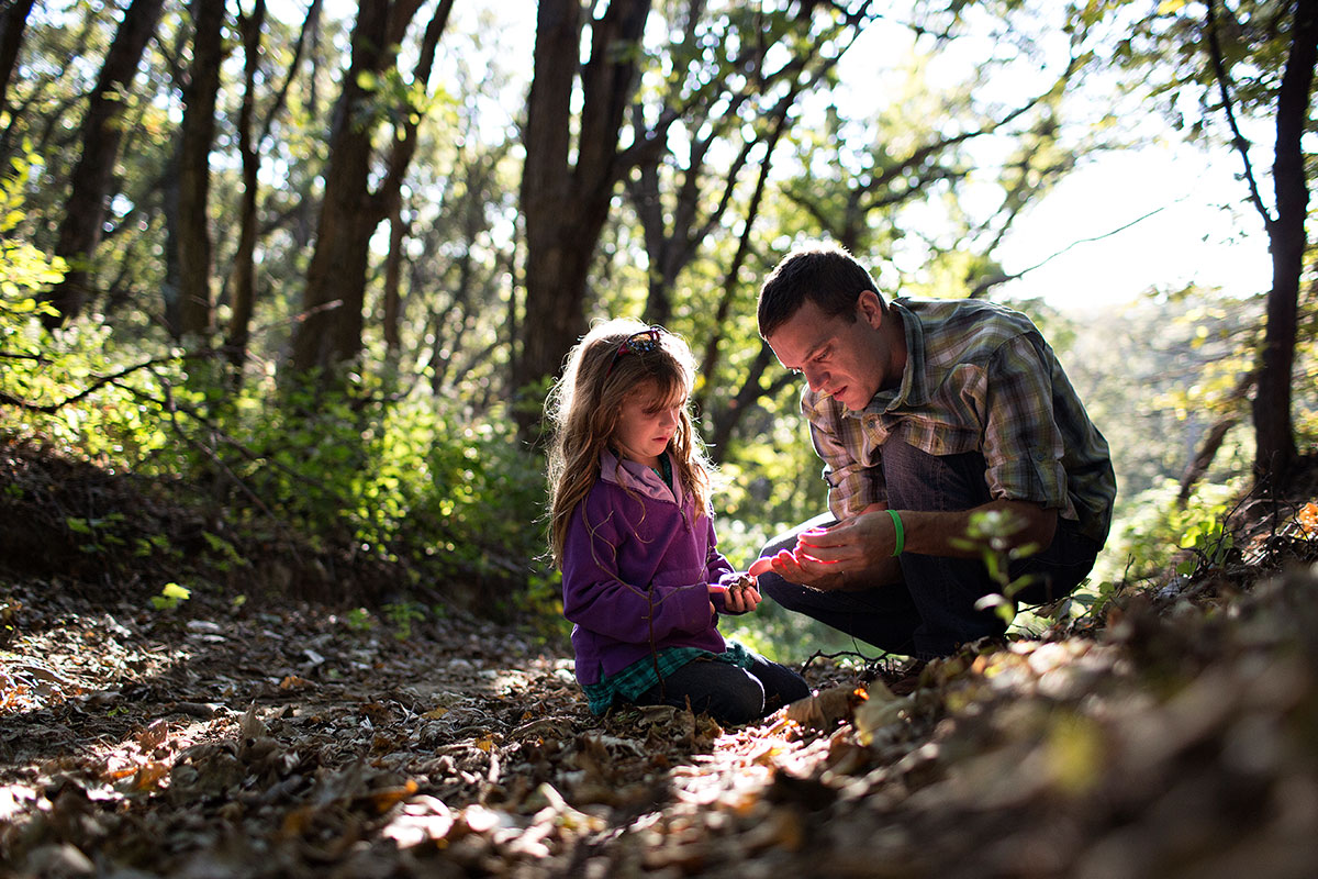 Father and daughter hanging out in the woods