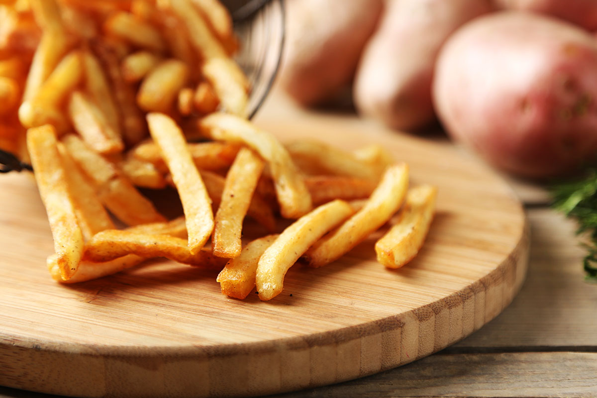 French fries on a round wooden board