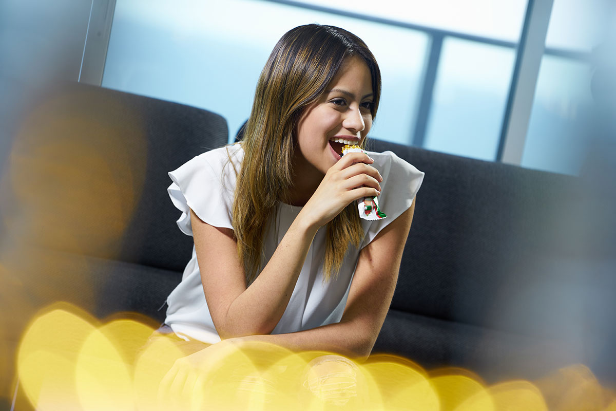 Young woman smiling while eating a cereal bar