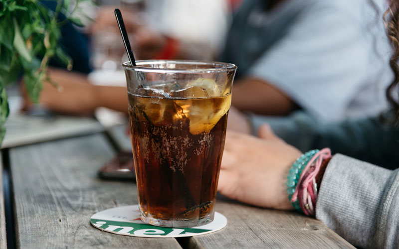 Glass of cola with lemon in a glass with a straw