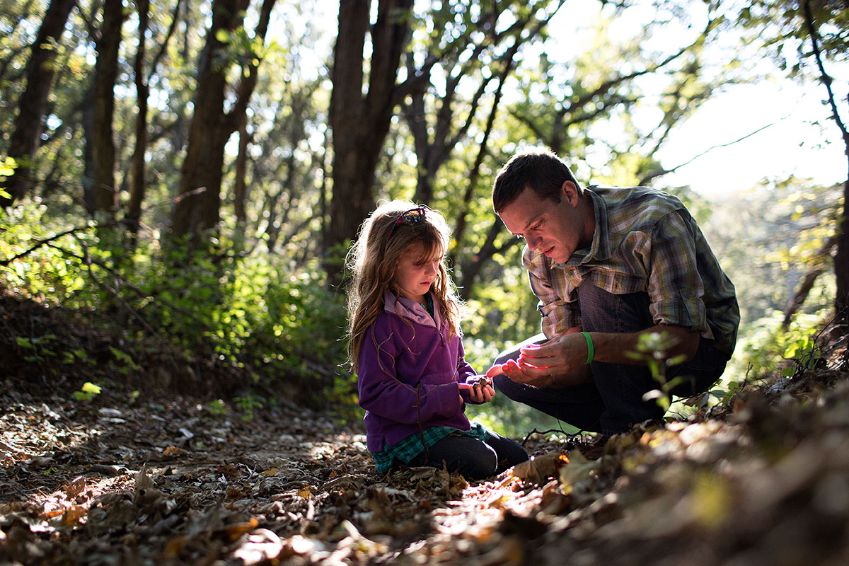 Man teaching his daughter about nature in Iowa, USA.