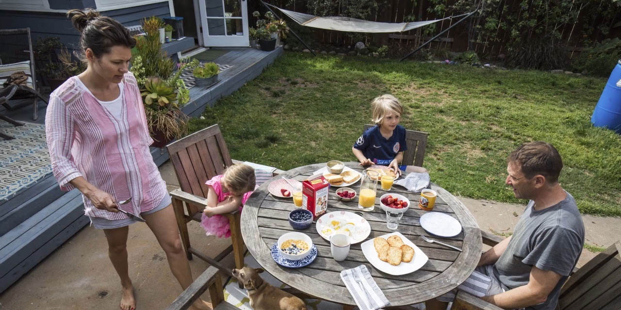 Family eating breakfast outside in their garden
